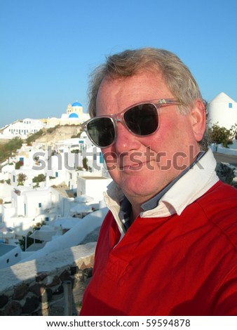 middle age male tourist in the Greek Islands Santorini with Cyclades architecture and church - stock photo
