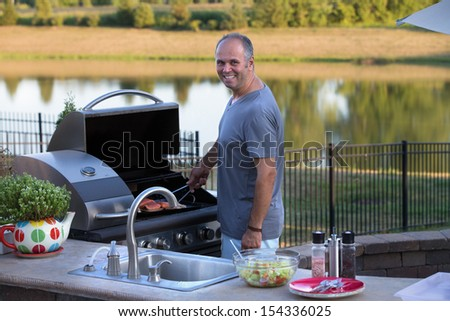 Middle age man cooking salmons at the outside kitchen barbecue