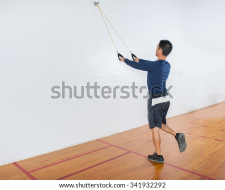 Middle age man demonstrates single leg straight pulldown strength exercise at start position.