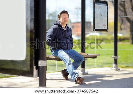 Middle age man sitting on bench on bus stop   - stock photo