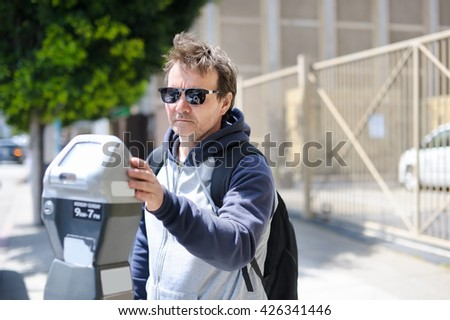 Middle age man using street parking meter in San Francisco, USA - stock photo