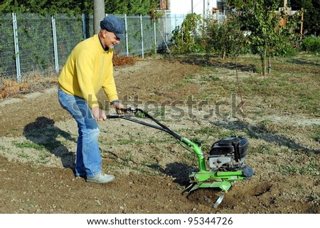 Middle age man with a rototiller in the garden - stock photo