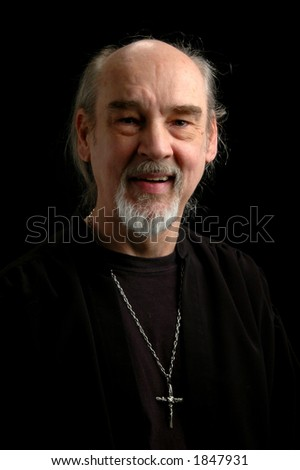 Middle age man with cross pendant over dark background