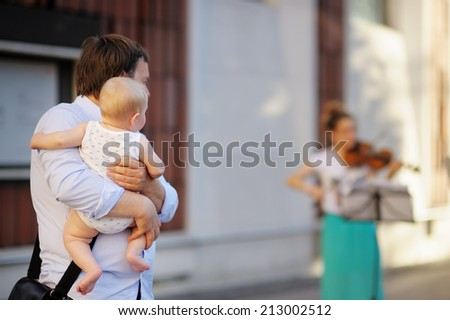 Middle age man with his little son listen fiddler  - stock photo