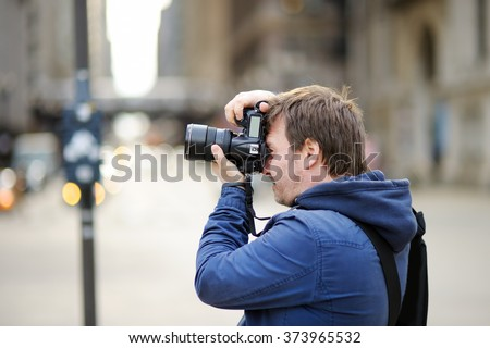 Middle age photographer taking photo with professional digital camera outdoors - stock photo