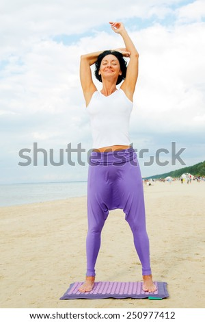 Middle age woman with shirt black hair in a white t-shirt and purple pants doing yoga on the summer beach. - stock photo