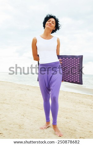 Middle age woman with shirt black hair in white t-shirt and purple pants posing on the summer beach. Rug for massage. - stock photo