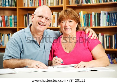 Middle aged adult education students studying in the library. - stock photo