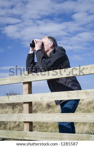 Middle aged adult male bird watching in the sand dunes, UK. - stock photo