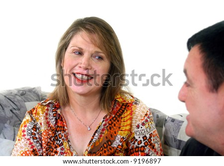 Middle aged adults chatting on a sofa and the woman with an inquiring look.