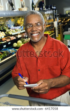 Middle aged African American man in grocery store holding shopping list and smiling at viewer.