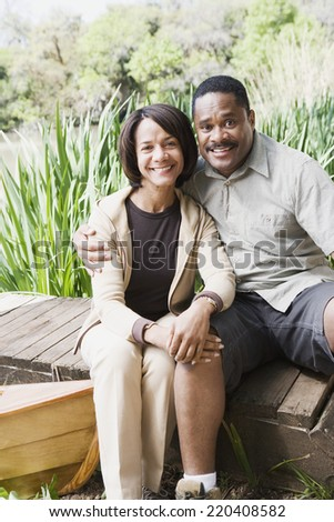 Middle-aged African couple smiling on dock - stock photo