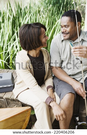 Middle-aged African couple smiling with fishing gear - stock photo