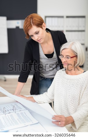 Middle Aged And Young Office Women Reading Business Documents at the Table Inside the Office.