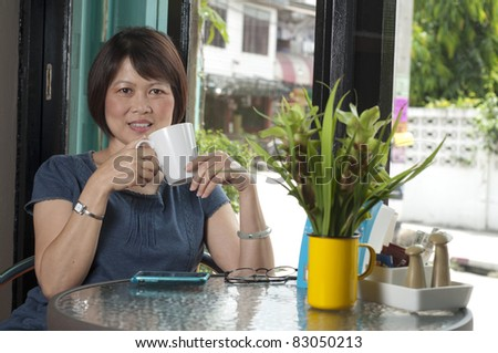 Middle aged Asian woman relaxing with a drink - stock photo