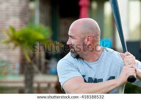 Middle-aged bald man playing holding baseball bat ready to swing.