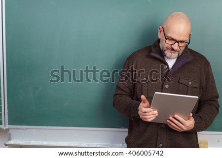 Middle-aged balding male teacher wearing glasses standing reading on a tablet computer in front of a blank chalkboard with copy space - stock photo