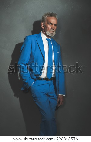 Middle Aged Bearded Businessman in Blue and White Formal Wear, Leaning Against the Wall and Looking at the Camera Seriously. - stock photo