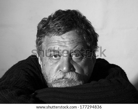 middle-aged bearded man in a sweater put his head in his hands - stock photo