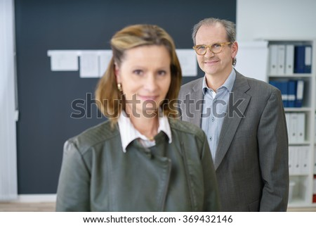 middle-aged business man and woman standing in the office