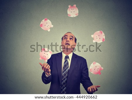 Middle aged business man juggling money piggy bank  - stock photo