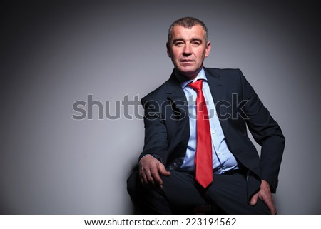 Middle aged business man sitting on a stool, resting his hand on his knee while looking at the camera. - stock photo