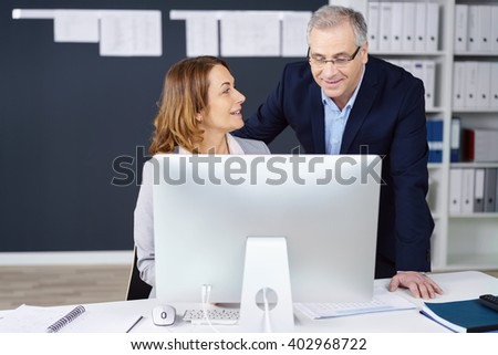 Middle-aged business partners in the office sharing a desktop monitor having a discussion concerning information online - stock photo