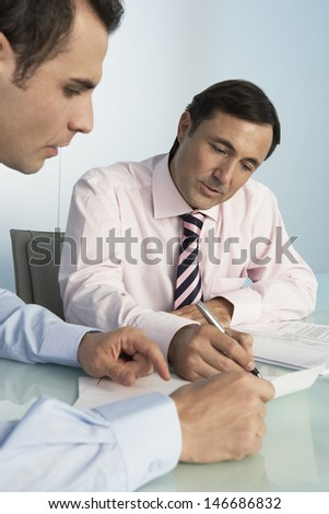 Middle aged businessman discussing over document with male colleague at desk in office - stock photo