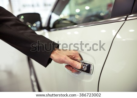 Middle aged businessman in classic suit is opening a car in a motor show, close-up - stock photo
