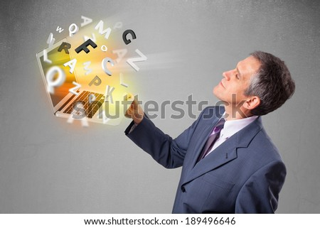 Middle aged businessman in suit holding laptop with colorful letters