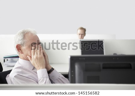 Middle aged businessman rubbing eyes at computer desk with colleague in background - stock photo