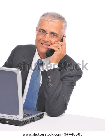 Middle Aged  Businessman seated at desk with laptop talking on cell phone isolated on white