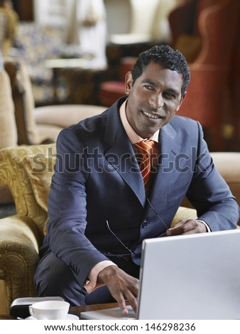 Middle aged businessman sitting in lobby and working on laptop - stock photo