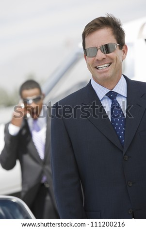 Middle aged businessman smiling with colleague using cell phone in the background at airfield - stock photo