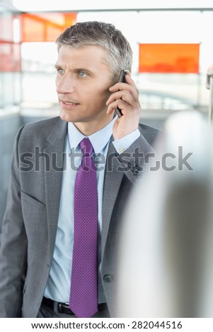 Middle aged businessman using cell phone at train station - stock photo