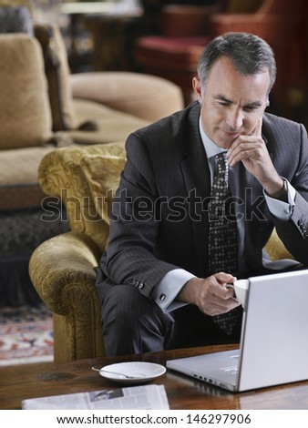 Middle aged businessman using laptop in the lobby - stock photo