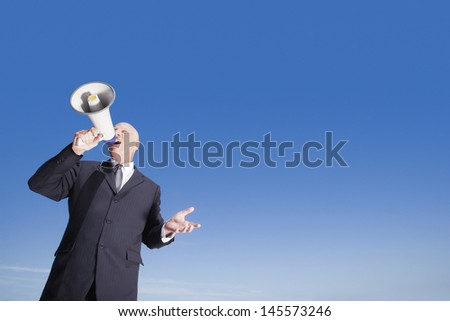 Middle aged businessman using megaphone against clear blue sky