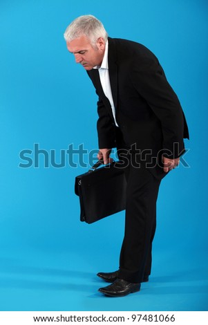 Middle-aged businessman with briefcase - stock photo