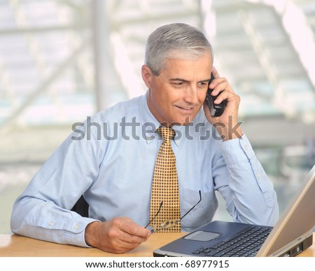 Middle aged businessman with laptop talking on telephone in modern office setting. Square format. - stock photo