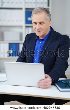 Middle-aged businessman working on a laptop in the office sitting reading information on the screen with a serious thoughtful expression