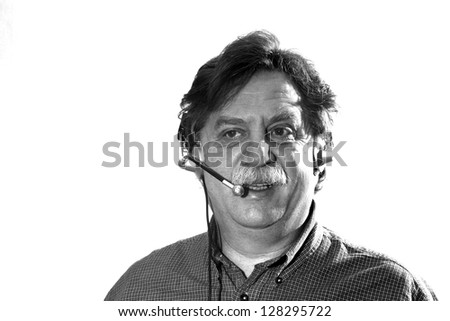 middle-aged businessman works in headphones with microphone behind computer, black and white - stock photo