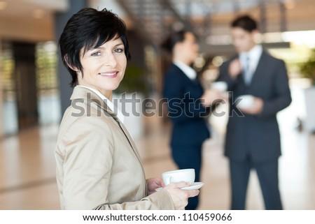 middle aged businesswoman having coffee break - stock photo