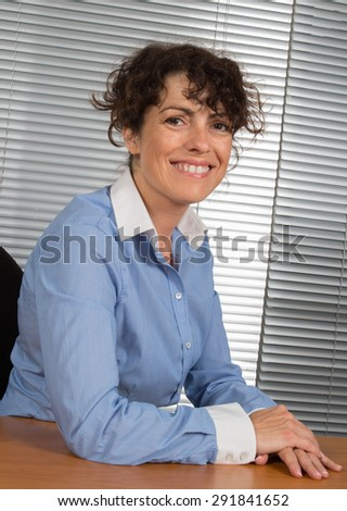Middle aged businesswoman in office looking at the camera