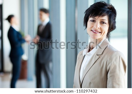 middle aged businesswoman in office with colleagues at background - stock photo