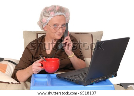Middle aged businesswoman in pyjamas working at home in bed, laptop on tray.  Making phone call