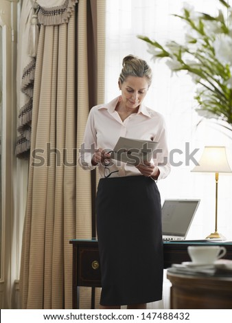Middle aged businesswoman reading document in home office