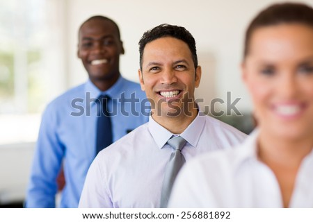 middle aged businesswoman standing in a row with business team - stock photo