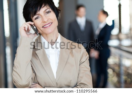 middle aged businesswoman talking on cell phone - stock photo