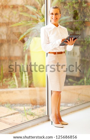 middle aged businesswoman using tablet computer in office - stock photo