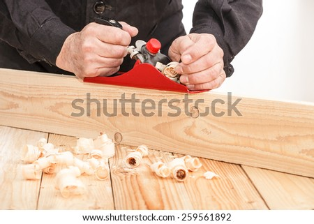 Middle aged carpenter planing the surface of a plank of wood  - stock photo